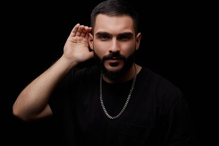 a dramatic portrait of a young serious guy, musician, singer, rapper with a beard in black clothes on a black isolated background. he puts his hand to his ear and listens.