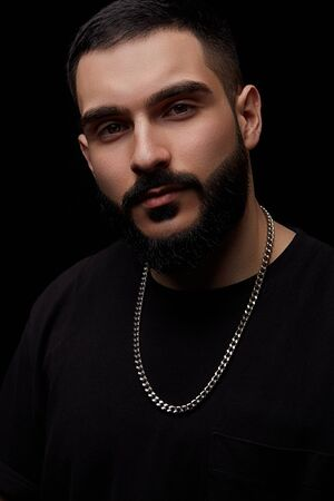 close-up of a dramatic portrait of a young serious guy, musician, singer, rapper with a beard in black clothes on a black isolated background.