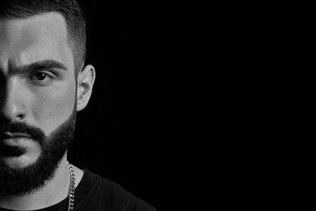 black-and-white close-up of a dramatic portrait of a young serious guy, a musician, singer, rapper with a beard in black clothes . half a face on a black isolated background.