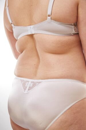 legs, buttocks and back of a 40-year-old woman with stretch marks, cellulite and excess weight on a white isolated background