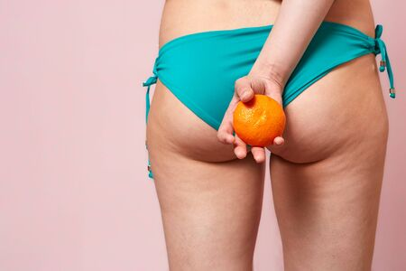buttocks with cellulite of a young girl in a blue swimsuit with an orange in her hands . on a pink isolated background