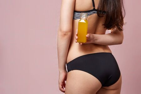 buttocks with cellulite of a young girl in a black swimsuit with an orange in her hands . on a pink isolated background. 스톡 콘텐츠