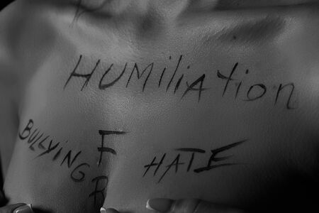 part of the body of a young girl with the inscription humiliation, hate, freedom. the inscriptions are written by the photographer's hand, not a tattoo . black and white photography.