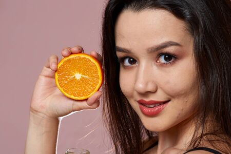 young beautiful slender Asian girl in a swimsuit . holding an orange. smiles. on a pink isolated background.
