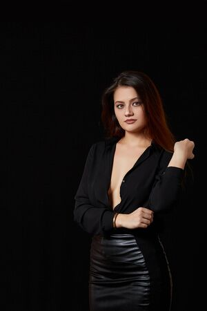 a young beautiful dark haired woman in a black unbuttoned shirt that revealed her Breasts and a black leather skirt on a black isolated background. Foto de archivo