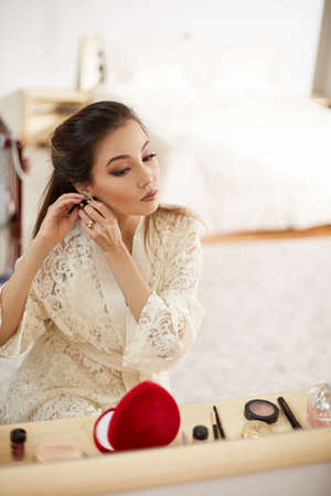 a young beautiful Asian woman in a beige lace dressing gown put on morning makeup and wears earrings. shallow depth of focus. selective focus. Stock Photo