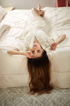 a young beautiful girl in a beige lace dressing gown is lying on her back on the bed in the bedroom.