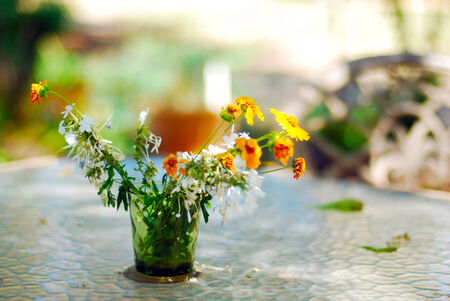Dry wilted bouquet of flowers on a table in the garden. photo