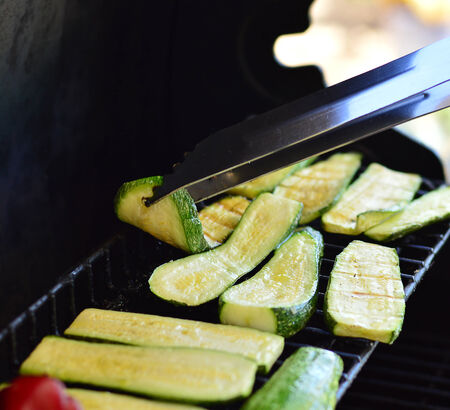 Grilled vegetables marinated in oil and spices on the grill outside.