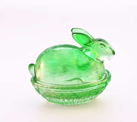 Candy dish green rabbit from glass on a white background. photo