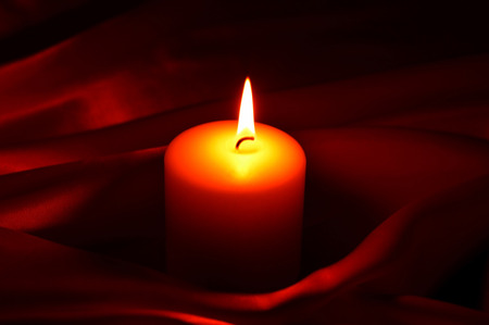 obscurity: White burning candle on a small dark background. Stock Photo