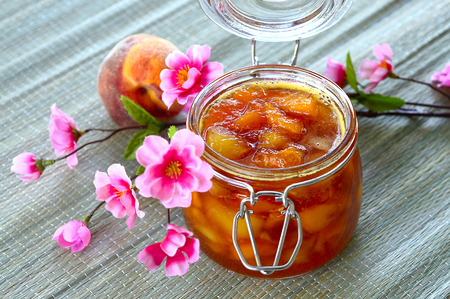 Nectarine peach apricot jam in a jar on the table.