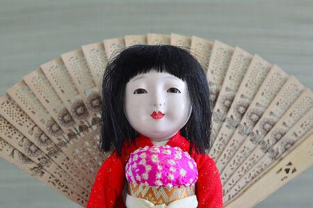 Japanese geisha doll with dark hair in a dress.