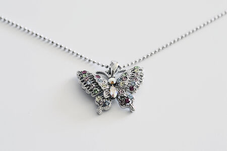 nicety: Butterfly pendant on a chain with stones of precious metals.