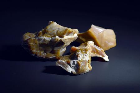 flint: Flint is very hard sharp stone on a black background.