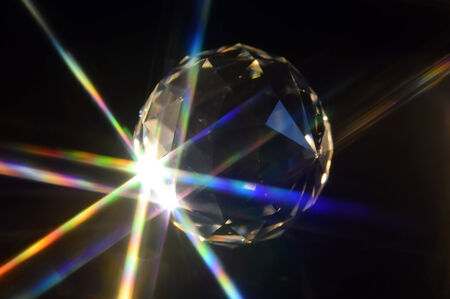 Crystal ball on black background with rays.