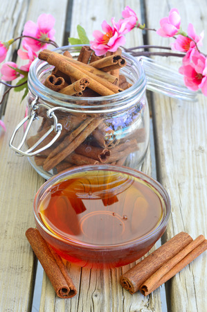 Fresh delicious honey in a bowl on the table near the cinnamon. Reklamní fotografie