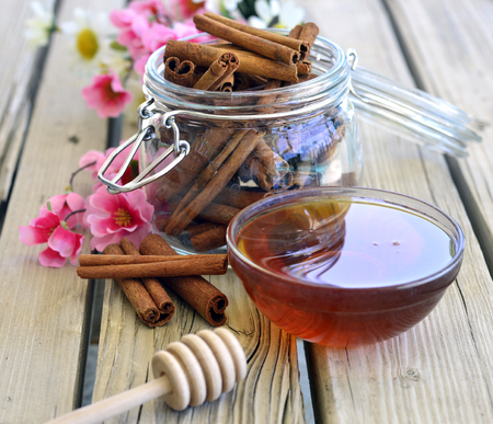 Fresh delicious honey in a bowl on the table near the cinnamon. Stock fotó