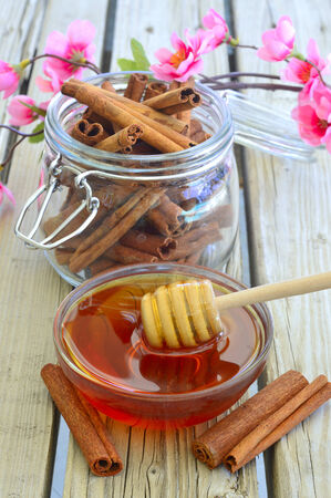 Fresh delicious honey in a bowl on the table near the cinnamon. Stock Photo