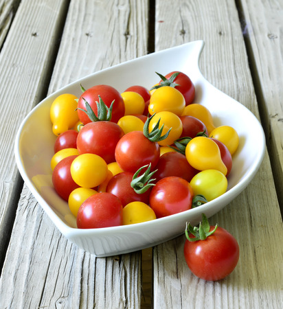 Cherry tomatoes are small ripe juicy fruit on the table. photo