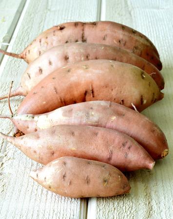 Sweet potatoes ripe juicy beautiful on a wooden table. photo