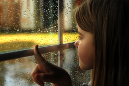 Girl and rain wet glass in autumn bad weather. photo
