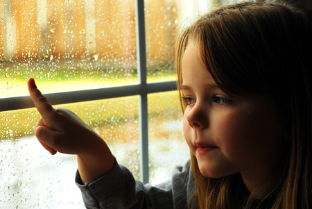 Girl and rain wet glass in autumn bad weather. Imagens