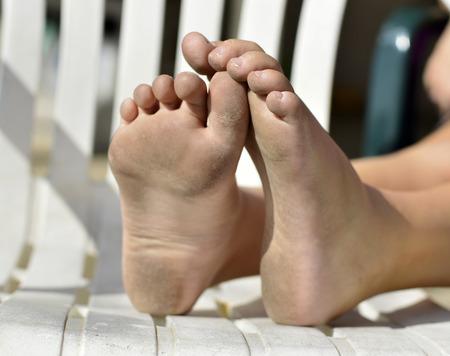 Vuile voeten stof vuil zand groezelige kind op een stoel. Stockfoto