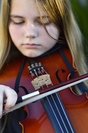 pre adolescent girl: Beautiful teen girl playing on a wooden violin Stock Photo