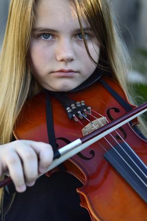 beautiful preteen girl: Beautiful teen girl playing on a wooden violin Stock Photo