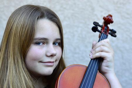 Muchacha adolescente hermosa que juega en un violín de madera Foto de archivo - 48358488