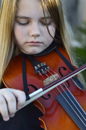 pre teen girl: Beautiful teen girl playing on a wooden violin Stock Photo