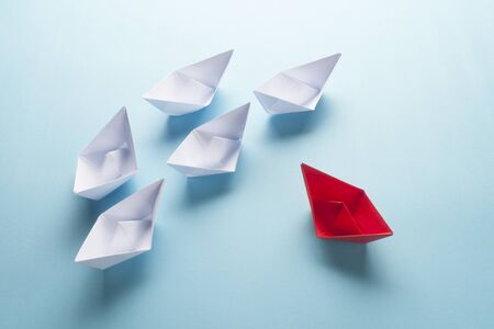 Group of origami boats on blue. One red paper boat with a group of white boats on blue. Team work concept.