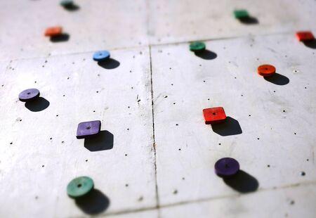 Colorful climbing holds on a grey climbing wall Standard-Bild