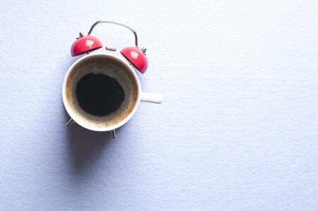 Morning coffee concept. Alarm clock and a cup of coffee all in one. Archivio Fotografico