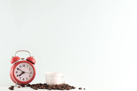 Red retro style alarm clock and fresh coffee. Morning concept.