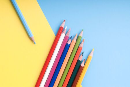 Coloufrul pencils on a blue and yellow background