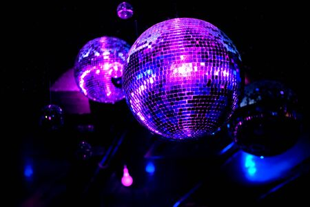 Shiny disco balls in blue and purple light.