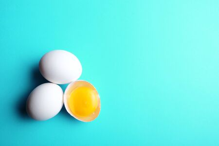 Three eggs with one broken on aquatic blue background. Group of three eggs. 版權商用圖片