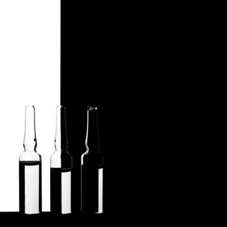 Ampules with vaccine on a minimalist black and white background.