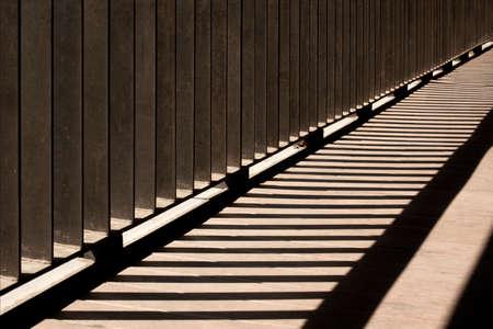 Harsh shade of a metal guard rail on a bridge. Banco de Imagens