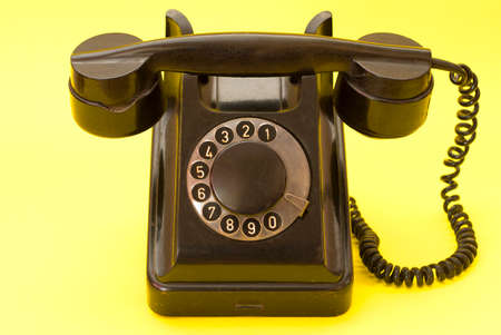 A retro style vintage telephone on a yellow background. Old landline telephone with a coiled cable. Banque d'images