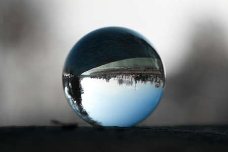 A riverside highway view through a lens ball. Glass ball with inverted view. 版權商用圖片