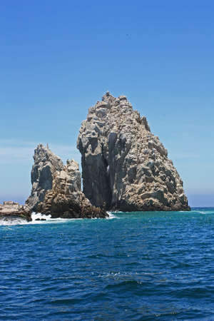 Large rock formation jutting up from the ocean off shore from Mexico.