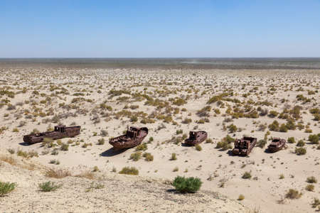 Rustic boats on a ship graveyards on a desert around Moynaq, Moynoq or Muynak - Aral sea or Aral lake - Uzbekistan, Central Asia