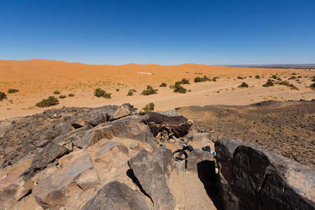 arid landscape in the big sand dunes of Erg Chebbi, Morocco, offer an amazing sight of sand and rocks of the Sahara desert Stok Fotoğraf