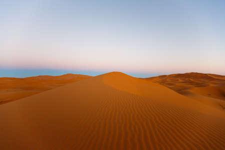 die großen Sanddünen von Erg Chebbi, Marokko, bieten einen erstaunlichen Anblick von Wellen und Formen und wechselnden goldenen, roten und orangen Farben während der Dämmerung und des Sonnenuntergangs Standard-Bild