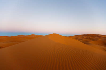 the big sand dunes of Erg Chebbi, Morocco, offer an amazing sight of waves and shapes and changing golden, red and orange colors during dusk and sunset Stockfoto