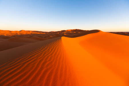 the big sand dunes of Erg Chebbi, Morocco, offer an amazing sight of waves and shapes and changing golden, red and orange colors during dusk and sunset