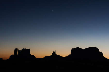 After Sunset and strong colors at the buttes in The Monument Valley, Navajo Indian tribal reservation park. Deep blue sky with cloudy and red sand dust in a rough plateau